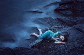 stock photo of sorrow  - Beautiful young woman on sea in twilight - JPG
