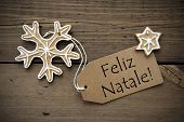 stock photo of ginger bread  - The Portuguese Words Feliz Natale which means Merry Christmas on a Label with some Ginger Breads on Wood - JPG