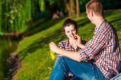 picture of love bite  - happy young couple bite grapes and enjoying picnic - JPG