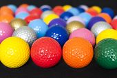 stock photo of miniature golf  - Assortment of colorful mini golf balls on black - JPG