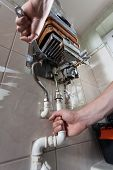 stock photo of pipefitter  - Plumber mending a gas water heater with a wrench - JPG