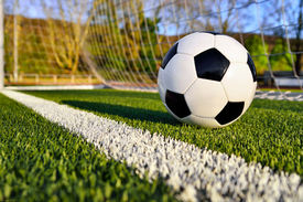 pic of football pitch  - Football lying on the green soccer pitch behind the goal line - JPG