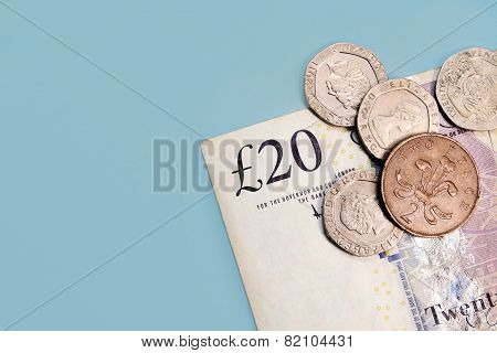Twenty pounds and pence coins isolated on blue