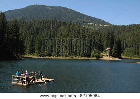General view of Sinevyr lake in Carpathian region with tourists sailing on the ferry, Ukraine