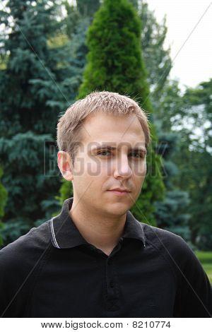 Retrato de hombre joven hermoso contra Parque de verano