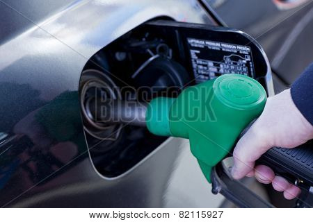 man filling up car with fuel at petrol station