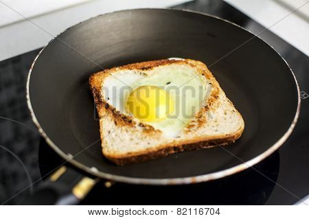 Slice of cereal toast bread with cut out heart shape full egg on black pan