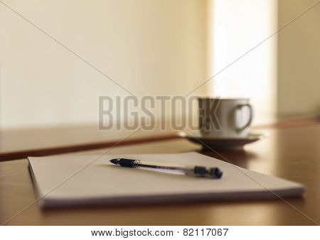 Cup And A Stack Of Papers On His Desk