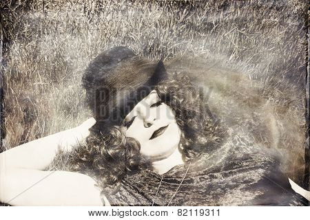 Woman in grass wearing top hat