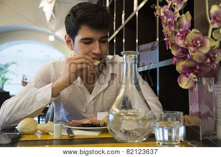 Attractive young man in elegant restaurant eating
