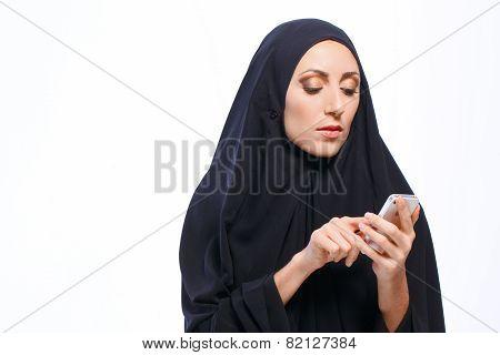 Beautiful Muslim woman holding a cellphone
