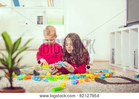 Two children playing with blocks selective focus