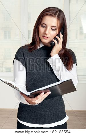 Girl Holds A Black Folder Open In One Hand And In The Other She Holds The Phone On Which She Says