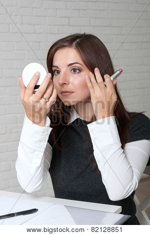 Girl In The Office Corrects Her Hair, Looking In A Small Mirror