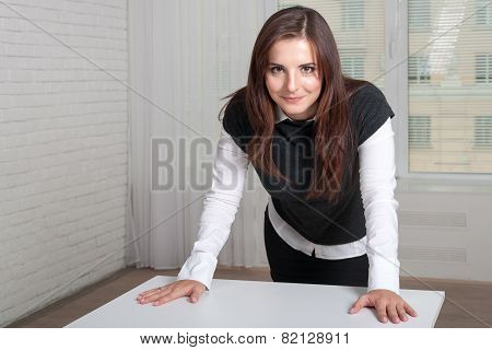 Girl In The Office Stands Propped Her Hands On The Table