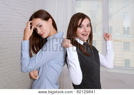 Two Women In Formal Clothes Standing Back To Back Against The Window