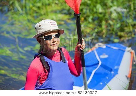 Girl near a kayak on the river