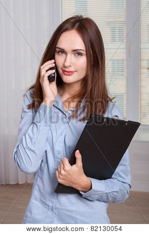 Girl Holding A Folder And Speaks By Phone