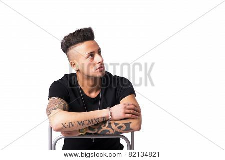 Trendy tattooed young man sitting on chair