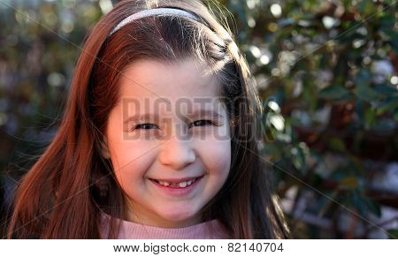 Little Girl With Brown Hair And Happy Expression