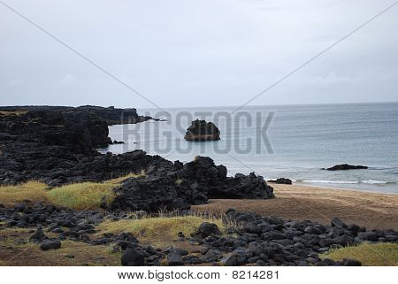 Golden beach amidst volcanic rock