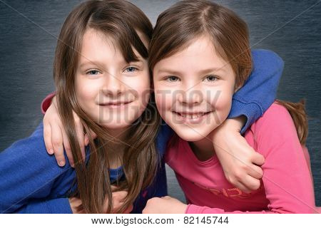 Two Cute Little Girl Friends Smiling At The Camera