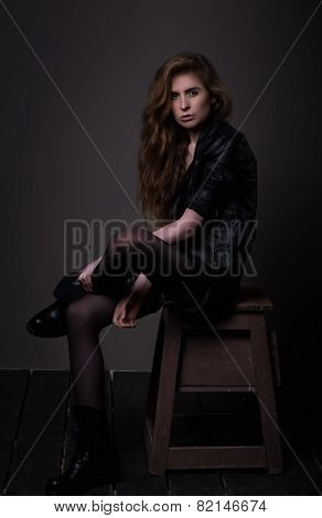 Sitting Attractive Woman In Black Dress And Leather Jacket