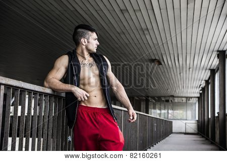 Muscular young man indoor wearing vest on naked torso