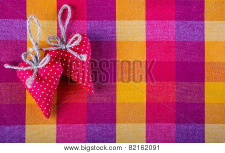 Red cloth two handmade hearts on checkered cloth napkin.