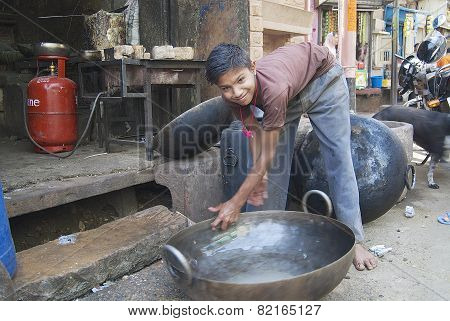 Teenager washes metal tub in Jodhpur, India.