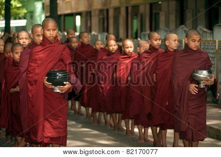 Row Of Buddhist Monks Waiting Lunch In Myanmar.