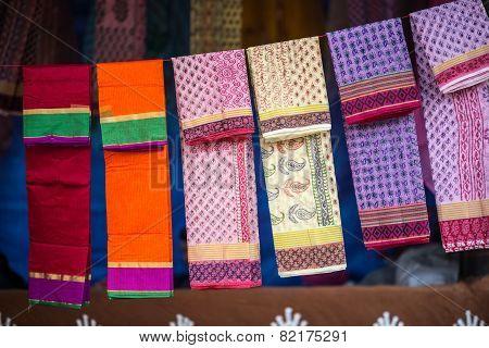 colorful fabrics and shawls at a market stall
