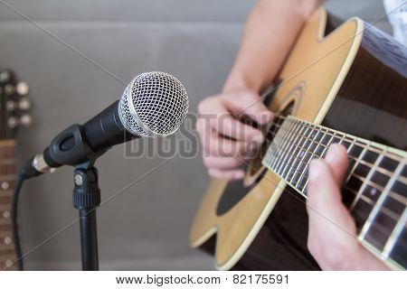 Guitarist Strumming A Guitar Into A Microphone