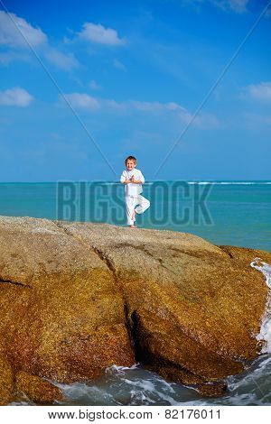 Cute Boy Kid  Practicing Yoga On The Rock In The Sea
