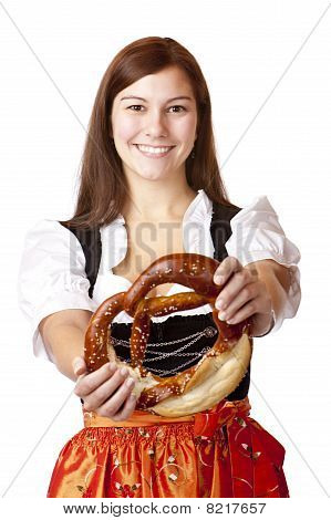 Portrait of young woman with Bavarian Dirndl dress holds Oktoberfest Pretzel.