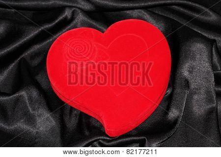 Heart-shaped jewelry casket placed on a black silk