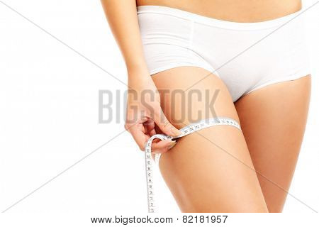 A midsection of a fit woman measuring her thigh over white background