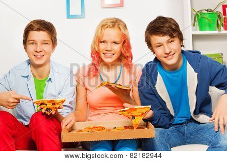 Three smiling friends hold pizza pieces and eat