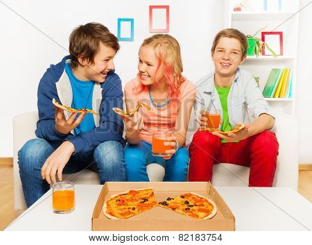 Happy smiling friends eat together pizza at home