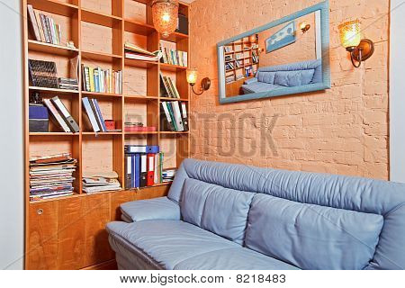 Part Of Cabinet Interior With Wooden Shelving And Blue Leather Couch