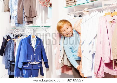 Blond small boy playa hide-and-seek in clothes