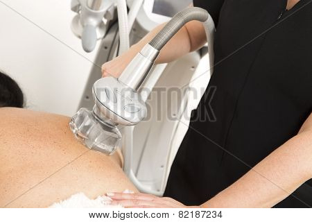 Client receiving vacuum treatment at body clinic