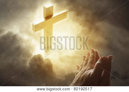 Hands praying and cross in sky
