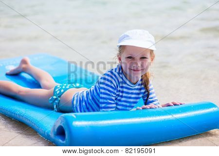 Little girl in a colorful sun protection swimwear on vacation swimming on floating mat in a shallow water at tropical lagoon