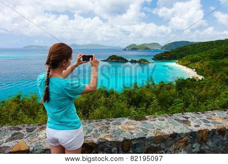 Back view of tourist girl taking photo with mobile cell phone of Trunk bay on St John island, US Virgin Islands considered by many as most beautiful beach in Caribbean