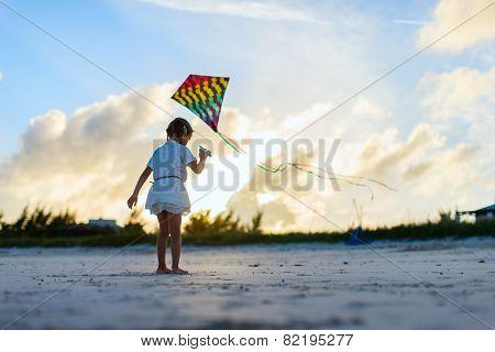 Little girl having fun flying a kite at beach during sunset