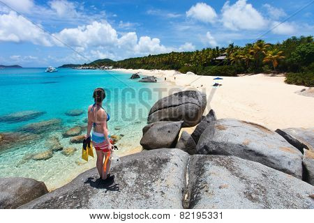 Young woman with snorkeling equipment enjoying view of a tropical beach standing on granite boulder at Virgin Gorda, British Virgin Islands, Caribbean