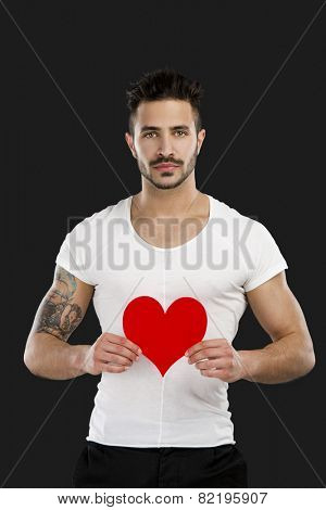 Handsome young man holding a hearth on is hands