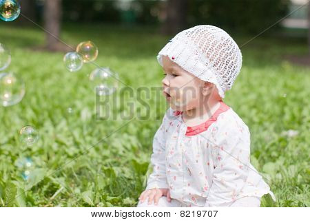 A Little Girl Sitting On Green Grass In The Park Looking At Soap