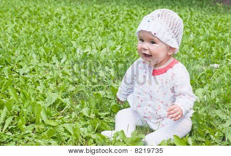 A Little Girl Sitting On Green Grass In The Park